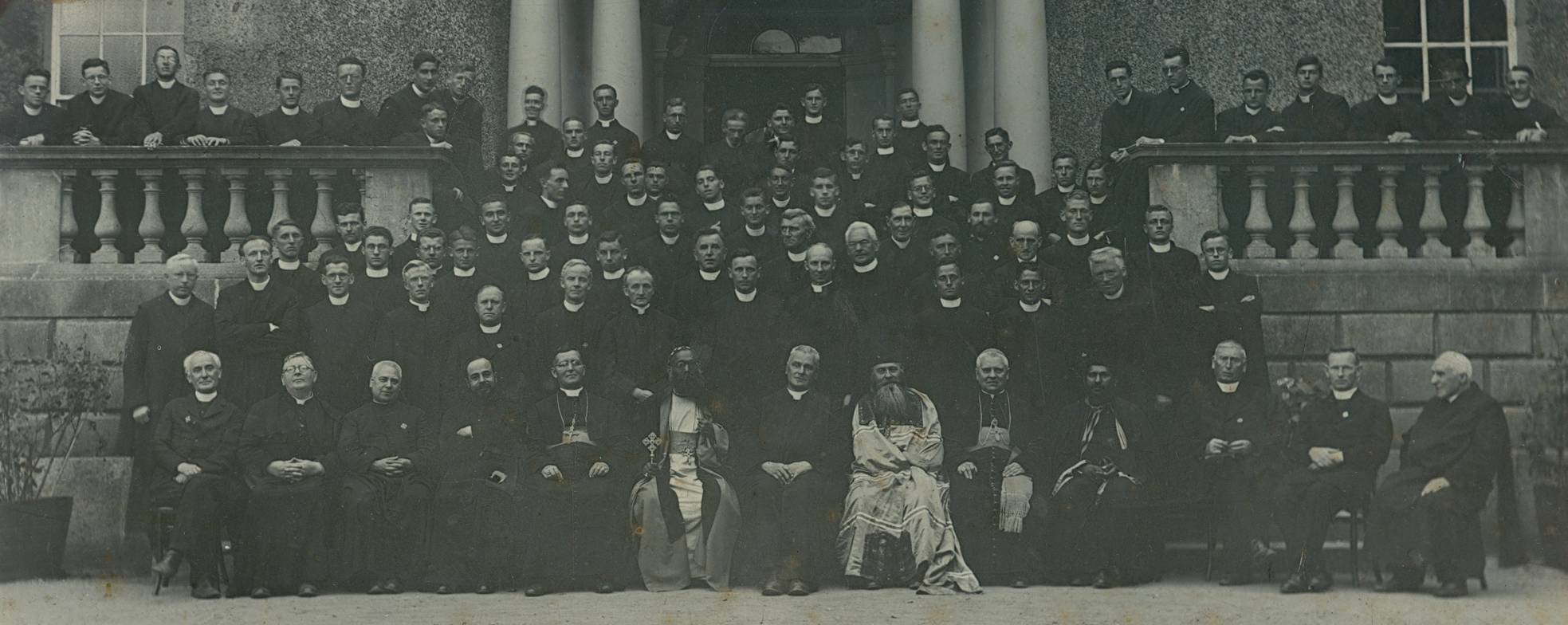 Jesuit community at Rathfarnham Castle, 1932 The Jesuit commnuity at Rathfarnham Castle on the occasion of the International Eucharistic Congress. Includes: Fr. T.V. Nolan SJ (Rector) and Irish Jesuits resident at Rathfarnham with guests; Mar Ivanios, Archbishop of Trivandrum, India; Bucys, Bishop of Olympus; Broderick, Bishop Peduelli; Trurita y Alumandos, Bishop of Barcelona; Rector of the Armenian Mission in Paris and Fr. Griffith, Vancouver. Rev. D.D. Ivanios and Bucys celebrated massess according to their respective Eastern rites in the chapel at Rathfarnham. FM/RATH/71. Courtesy of the Irish Jesuit Archive.